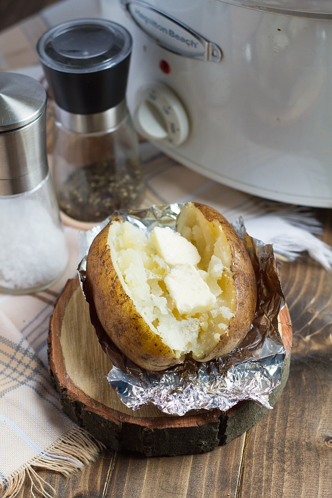 baked potato with butter on foil on wooden log round with beige and black plaid cloth underneath; salt and pepper and white slow cooker in background