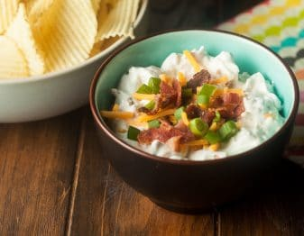 Loaded baked potato dip with orange cheddar, green onion, and bacon bits topping it in bowl that is brown outside and light blue inside; white bowl with rippled potato chips in top left corner; right corner has cloth with wave stripe in yellow, green, blue, black, orange, pink