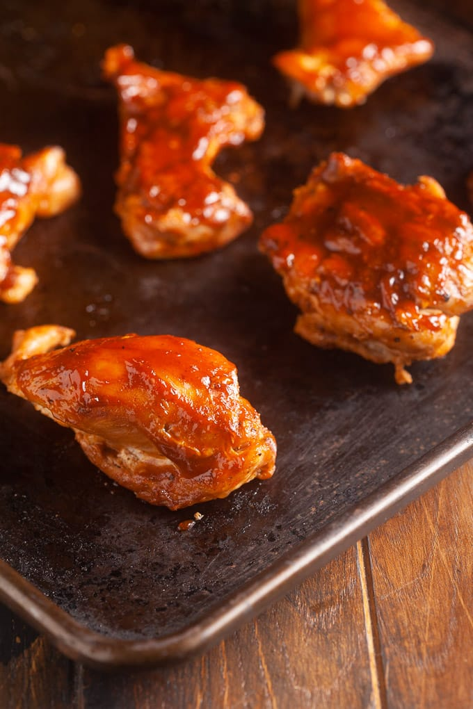 chicken thighs with bbq sauce on them on sheet pan