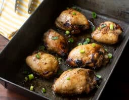 baked chicken thighs in metal baking pan with green onion garnish; yellow and white striped towel and tongs in background