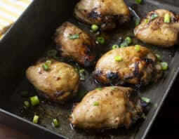 baked chicken thighs in metal baking pan with green onion garnish; yellow and white striped towel in background