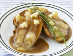 3 baked potato halves on white plate with 2 black stripes around lip on white tablecloth with blue stripes. gravy and somewhat melted cheese curds on top of potatoes sprigs of chives garnish on top; green cloth with small dots underneath plate