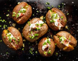 6 baked potatoes on baking tray with cream cheese, chives, and kosher salt