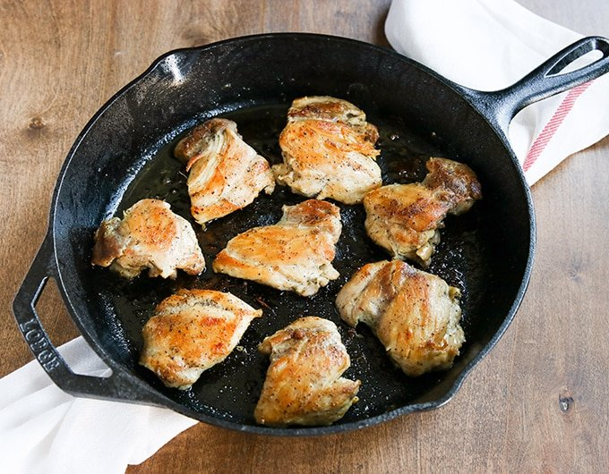 browned chicken thighs in large lodge cast iron skillet; white cloth with red stripe underneath skillet; on brown wood table