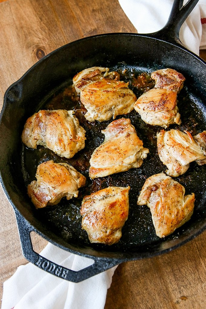 browned chicken thighs in large lodge cast iron skillet; white cloth underneath skillet; on brown wood table