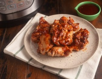 white plate with black speckles on white cloth with black stripes; chicken thighs with bbq sauce on plate; instant pot in background and light green condiment bowl with bbq sauce in it in background