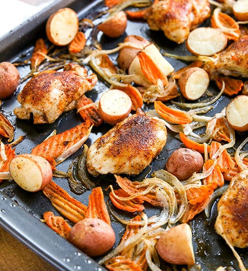 sheet pan with halved baby red potatoes, carrot chips, onion slices, and seasoned chicken thighs