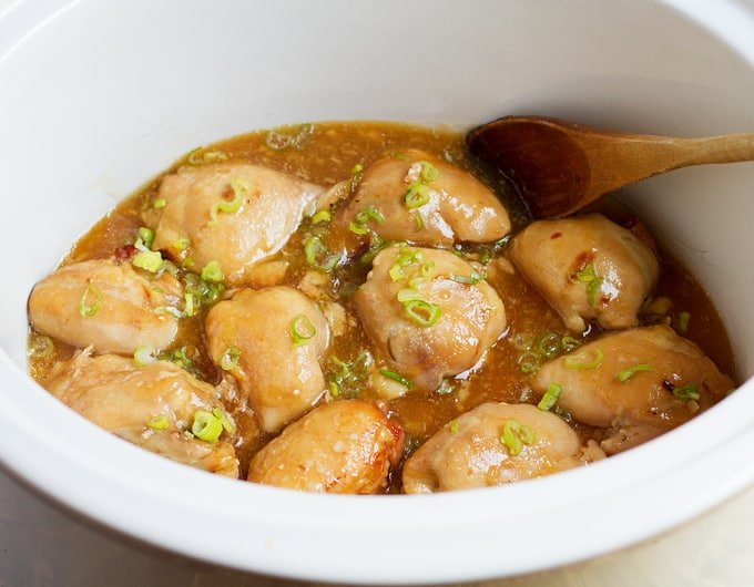 8 chicken thighs in white crock with chopped green onion on top in a light brown broth; wooden spoon in crock