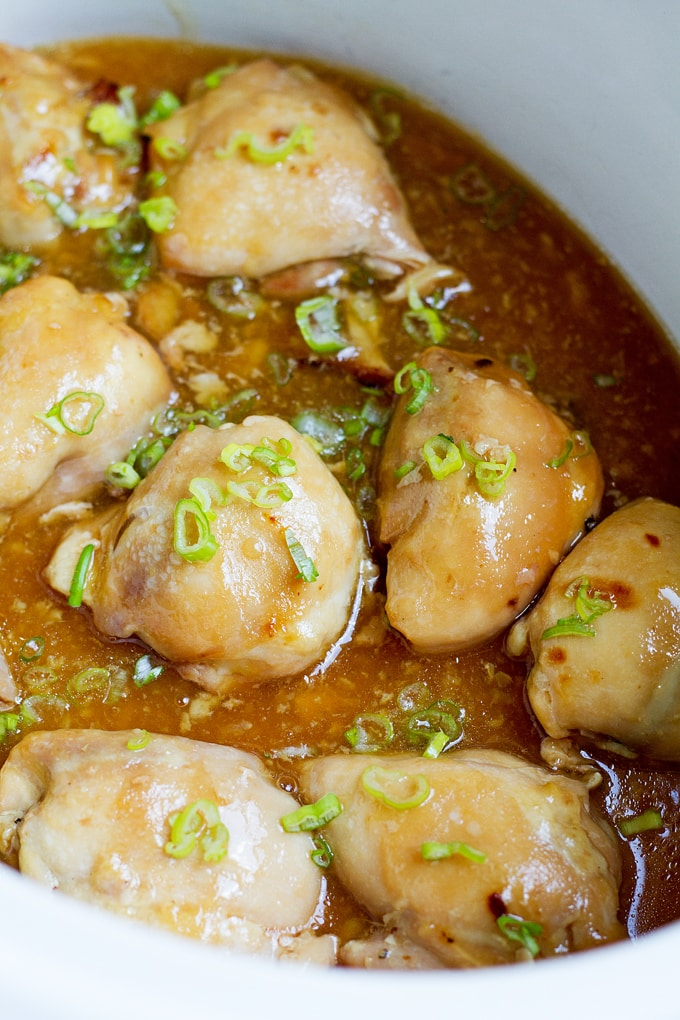 8 chicken thighs in white crock with chopped green onion on top in a light brown broth