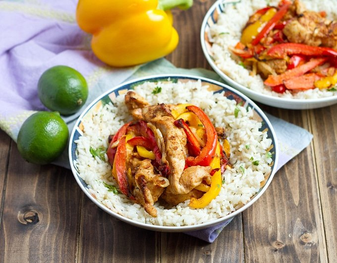 strips of seasoned chicken, red, and yellow bell peppers in bowl on top white rice with cilantro and black pepper; another bowl with same ingredient in background; 2 limes to left of bowl and yellow bell pepper behind bowl; light lavender cloth under bowl and produce