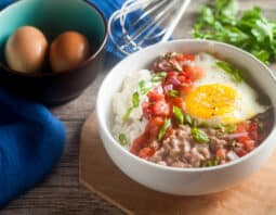bowl with rice, dollop of sour cream, salsa, sunnyside up egg, refried beans, and chopped green onion garnish on light brown platter; cilantro and whick behind bowl; dark brown bowl with robin egg blue interior with 2 brown eggs in it and a bright blue cloth behind the bowl