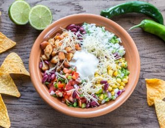 terracotta colored bowl with rice, chopped green onion, corn, chopped red onion, chicken, chopped tomato, black beans, pico de gallo, diced peppers, and shredded white cheese with dollop of sour cream; to left and right of bowl, tortilla chips scattered; 2 lime halves behind left of bowl; 2 serrano peppers behind right of bowl