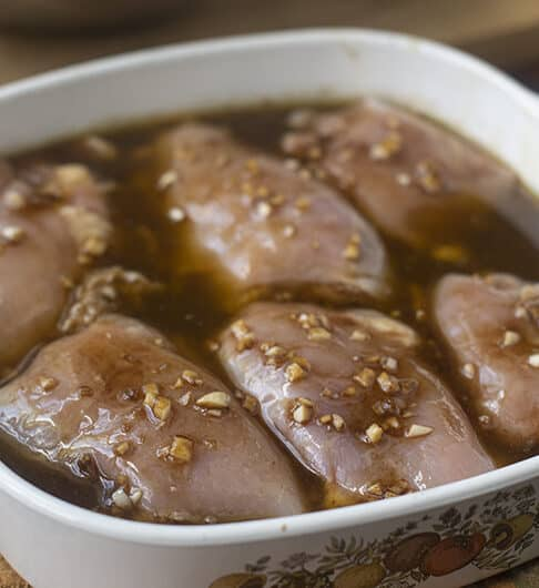 chicken thighs in small white casserole dish with handles; sitting in brown marinade liquid with minced garlic