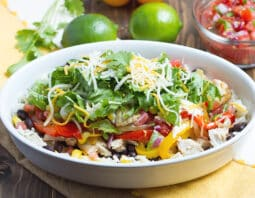 oblong white bowl with rice with cubes of chicken, slices of red and yellow bell pepper, lettuce, and white and orange shredded cheese; white, yellow, and beige striped cloth under bowl; cilantro, lime, and fresh salsa in condiment bowl