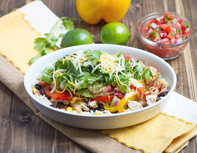oblong white bowl with rice with cubes of chicken, slices of red and yellow bell pepper, lettuce, and white and orange shredded cheese; white, yellow, and beige striped cloth under bowl; cilantro, lime, yellow bell pepper, and fresh salsa in condiment bowl