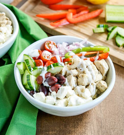 white bowl with rice, chicken, kalamata olives, cucumber, green and red bell peppers, halved cherry tomatoes with white sauce drizzled over; cutting board in background with orange bell pepper, lemon, and cucumber; medium colored green cloth behind bowl