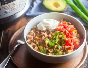 white bowl with cooked rice base with corn, black beans, and onion topped with chopped green onion, salsae, and a dollop of sour cream; fork to left of bowl; green onion and half avocado in background on light blue cloth; bottom part of instant pot showing in top left corner