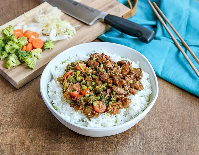 white bowl with rice topped with beef, carrots, broccoli, and onion mixture; light blue cloth in background on right with chopsticks on it; back left has a small cutting board with chef's knife, chopped broccoli, carrots, and onion