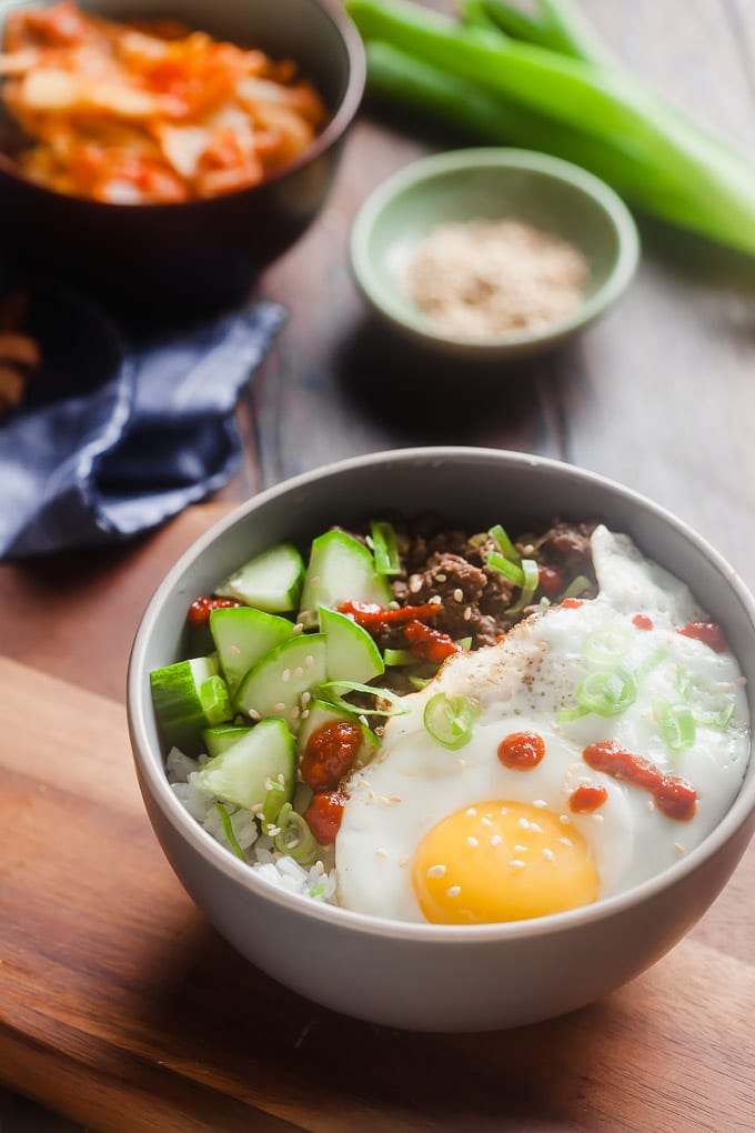 white bowl with rice topped with cucumber, beef, green onion garnish, sesame seeds, sunnyside up egg, and drizzle of sriracha; in background, blurred out condiment bowl, green onion,and bowl with something orange in it; dark blue cloth under bowl