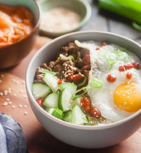 white bowl with rice topped with cucumber, beef, green onion garnish, sesame seeds, sunnyside up egg, and drizzle of sriracha; in background, blurred out condiment bowl, green onion,and bowl with something orange in it; light blue cloth in front left corner; sesame seeds on table