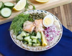 rice in bowl topped with cucumber, salmon, fresh dill, capers, half hard boiled egg, chopped red onion, and lemon wedge; dark blue cloth under bowl; cutting board in background with cucumber rounds, lemon, wedges, and dill