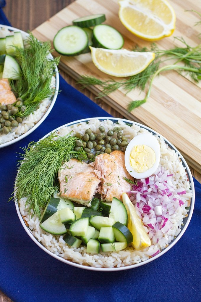rice in bowl topped with cucumber, salmon, fresh dill, capers, half hard boiled egg, chopped red onion, and lemon wedge; dark blue cloth under bowl; cutting board in background with cucumber rounds, lemon, wedges, and dill; edge of second bowl of food in picture
