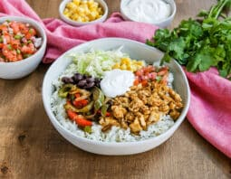 white bowl with rice topped with sauteed green and red bell pepper slices, black beans, shredded lettuce, corn, fresh pico de gallo, sofritas, and dollop of vegan sour cream; pink cloth in background as well as left to right: condiment bowl of pico de gallo, corn, sour cream, and a bunch of cilantro
