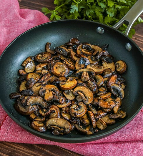 frying pan with sliced sauteed mushrooms with bright pink cloth underneath; parsley in background