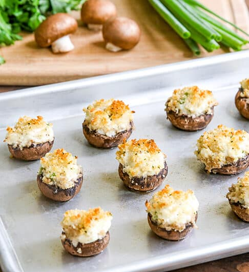 silver baking tray with stuffed mushrooms on it; cutting board in background with parsley, crimini mushrooms, and green onion top