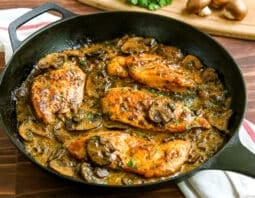 cast iron pan with chicken breast in mushroom sauce with green garnish; white cloth with red stripe underneath; cutting board in background with crimini mushrooms and parsley garnish