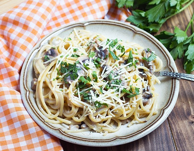 spaghetti with mushrooms, parsley, and shredded cheese; orange and white gingham cloth to left of plate; fresh parsley bunch in back right corner of picture