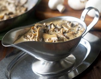 stainless steel gravy boat with mushroom gravy in it; brown cutting board with white mushrooms on in background and edge of pan with gravy in it in back left