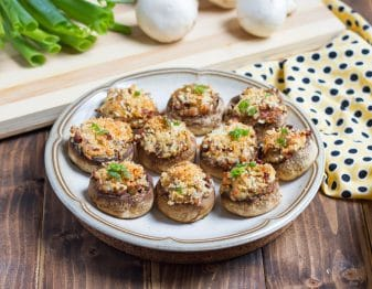 white plate with brown strip around edge with stuffed mushrooms topped with breadcrumbs and green onion garnish; ellow cloth to right with black polka dots; background has a light brown striped cutting board with a bit of green onion tops showing