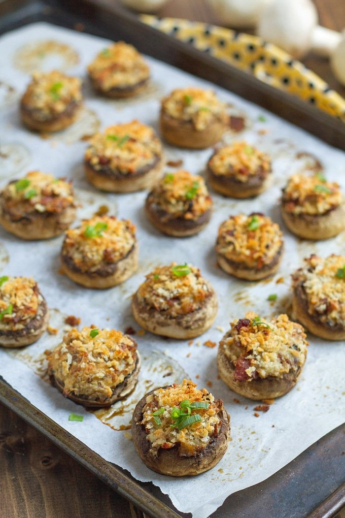 stuffed mushrooms topped with green onion garnish on a baking sheet with parshment paper under them; in background blurred out yellow cloth with black polka dots