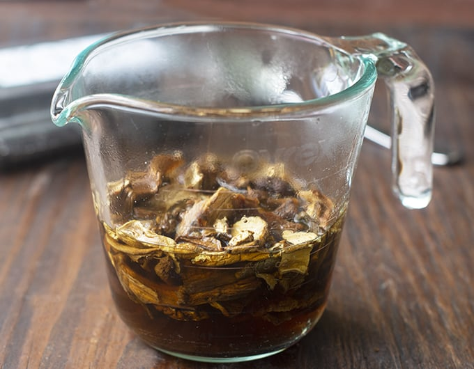 measuring cup with dried mushrooms soaking in water in it