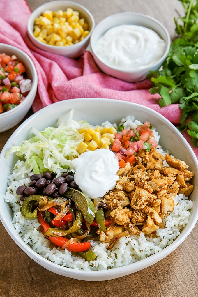 white bowl with rice sofritas, vegan sour cream, black beans, sauteed red bell peppers and onions, corn, pico de gallo, and lettuce; pink cloth in background and cilantro
