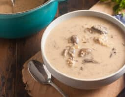 creamy mushroom soup in white bowl with spoon to left and natural wood board under bowl; medium blue cloth to right; parsley garnish in background; back left has partial of a le creuset teal pot with mushroom soup and ladle in it
