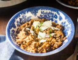 mushroom risotto garnished with cheese and sprigs of fresh thyme in white and blue porcelain bowl; fork to right of bowl; to left of bowl medium blue cloth