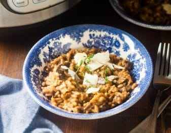 mushroom risotto garnished with cheese and sprigs of fresh thyme in white and blue porcelain bowl; fork to right of bowl; to left of bowl medium blue cloth; part of instant pot shown in background