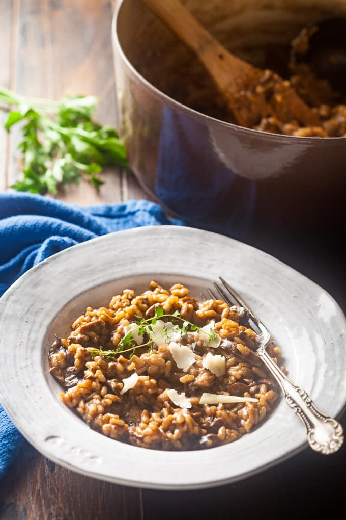 mushroom risotto garnished with cheese and fresh thyme sprigs; fork in bowl; bright blue cloth to back left; sprig of green herb in background and pot with risotto and wooden spoon in it