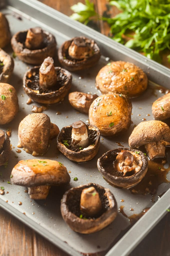 whole baby brown/crimini mushrooms on baking sheet with mushroom liquid and green herb garnish; green parsley bunch in background
