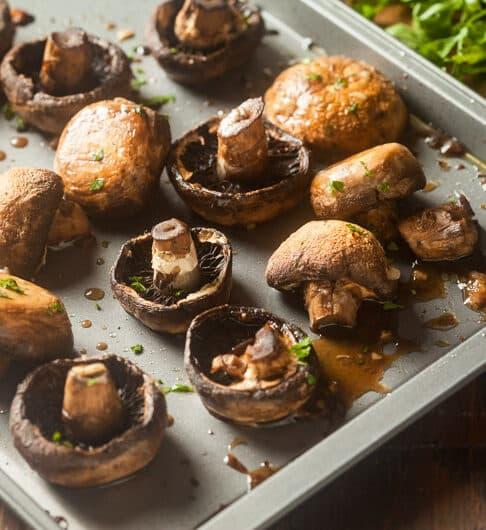 whole baby brown/crimini mushrooms on baking sheet with mushroom liquid and green herb garnish; green parsley garnish in background