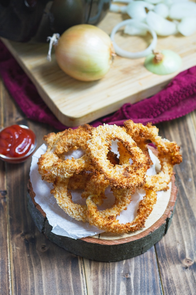 onion rings piled on a round wooden board with paper towel on top; little condiment bowl with ketchup in it to right; onion to left; burgundy cloth in the background with cutting board on it with an onion and sliced onion rings