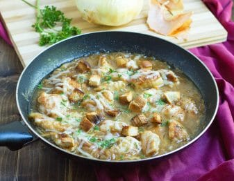 frying pan with pieces of chicken and croutons in french onion soup topped with melted cheese and fresh parsley; plum colored clothto right of pan and cutting board in background with fresh parsley and onion