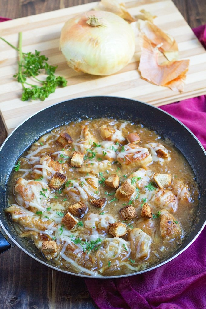 chicken topped with French Onion soup, cheese, chopped parsley, and croutons; parsley and an onion on cutting board in background