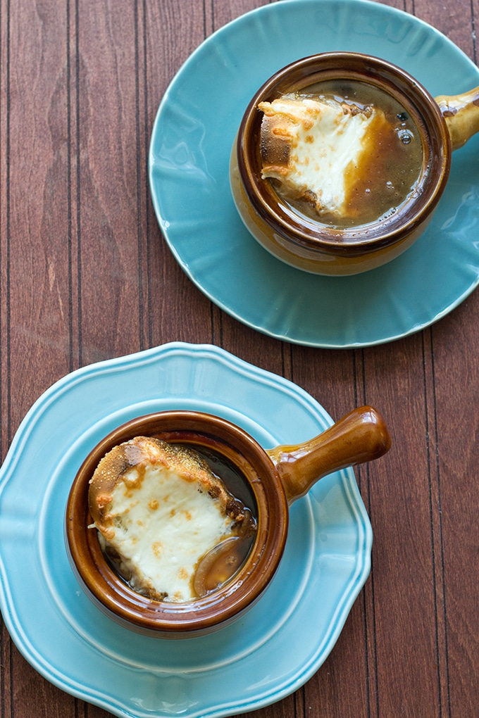 2 light blue plates with a brown long handled crock of french onion soup with a piece of toasted baguette and melted cheese