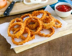 fried onion rings on a wooden board with a paper towel under it; white condiment bowl on background with ketchup; light blue cloth in back right corner; cutting board in background with uncooked onion rings and knife