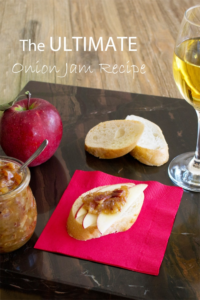 red paper napkin with baguette slice on top with 3 apple slices and a dollop of onion jam with bacon in it; 2 slices baguette in background, 1 red apple in back left corner and jar of onion jam in front corner with small spoon in it; glass of white wine on right side