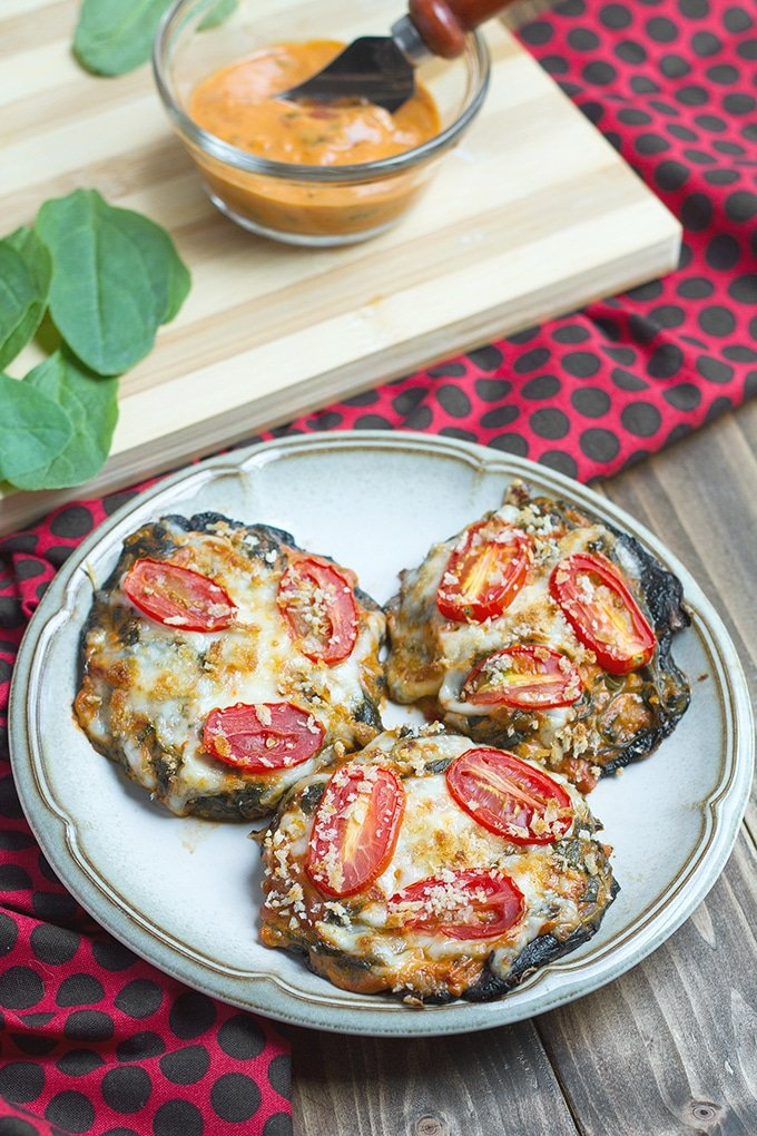 3 portobello mushrooms on white plate with brown stripe around edge; mushrooms are topped with cheese, slices of tomato and breadcrumbs; red cloth with black polka dots in background; light brown cutting board on top of cloth with spinach leaves and orange sauce in condiment bowl