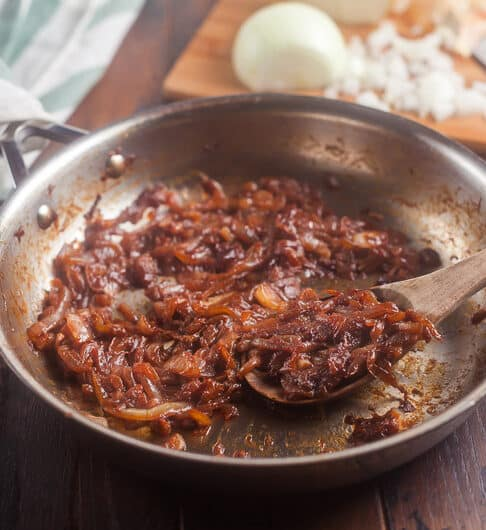 caramelized onions in a stainless steel frying pan with a wooden spoon in pan; white and green striped cloth in background; cuttiong board in background with partially chopped onion and knife